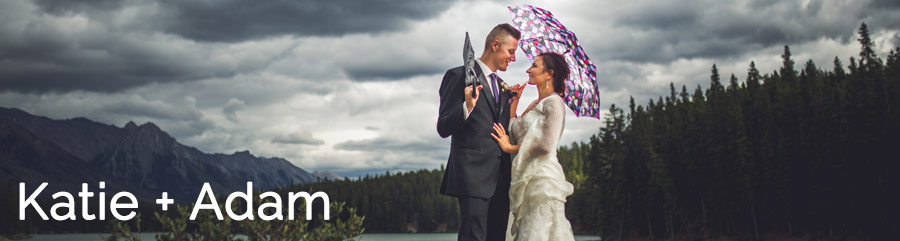 groom and bride with umbrella stormy skies in the rocky mountains canmore cornerstone theatre wedding