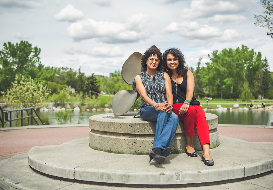 mother daughter sitting by statue at prince's island park