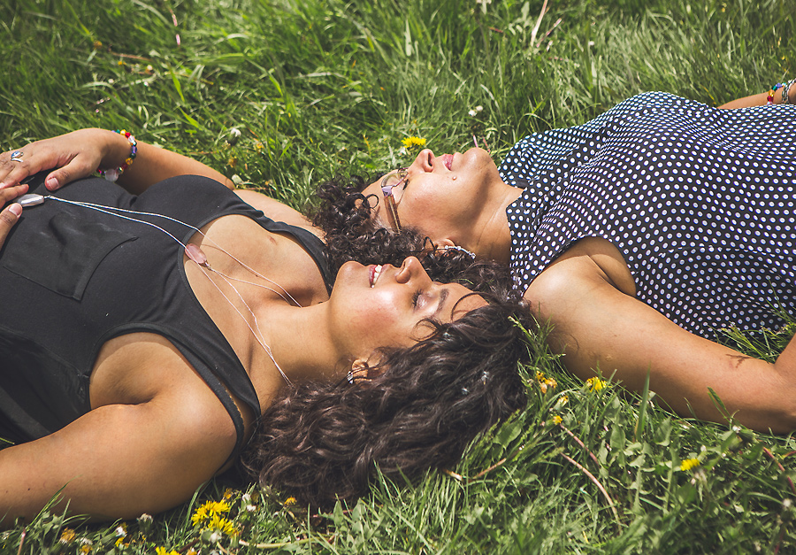 mother and daughter resting on grass with eyes closed