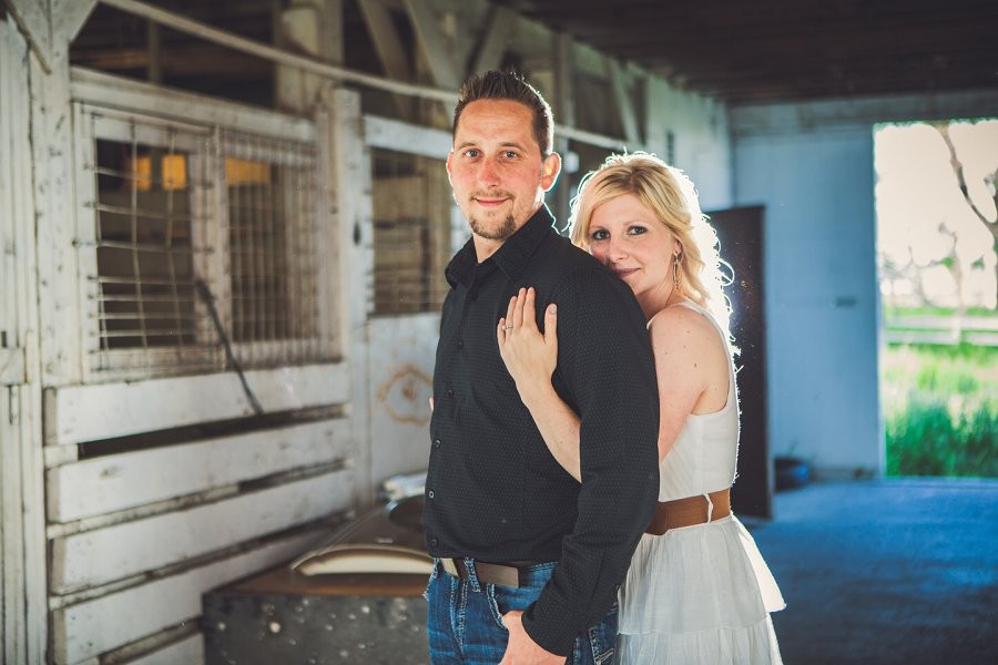 woman holding man behind back cowboy style couple engagement session