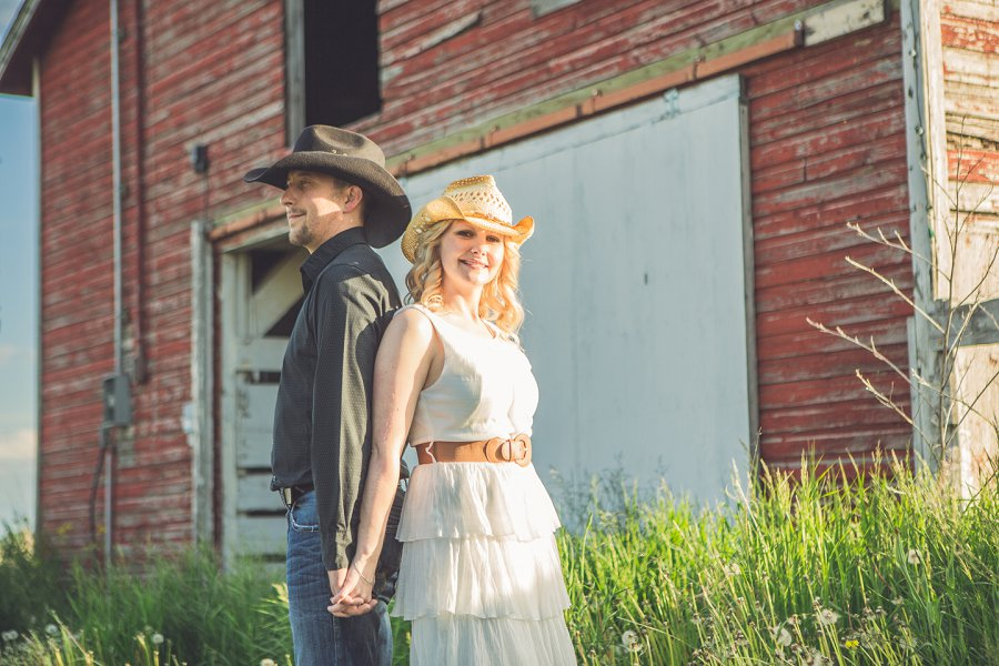 couple holding hands outside red barn cowboy style engagement session