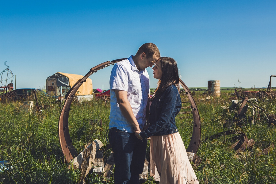 couple in front of large wheel rustic engagement session anna michalska calgary