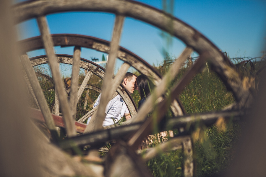 couple kissing behind wheels rustic engagement session calgary anna michalska