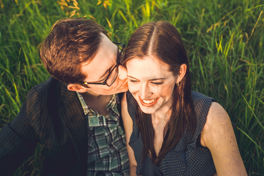 couple kissing sitting in grass golden hour engagement session