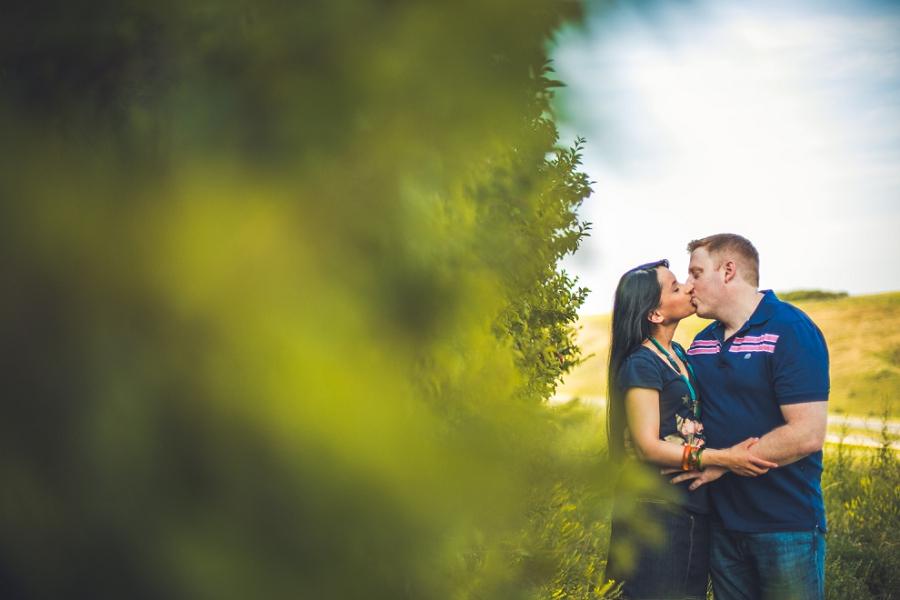 couple by bush sunset engagement session calgary