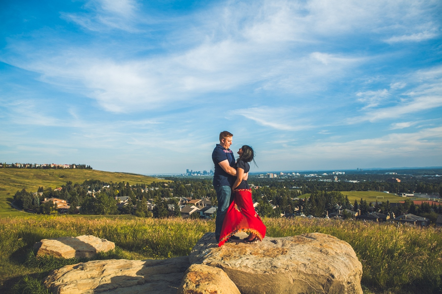 couple with red sash overlooking calgary sunset engagement