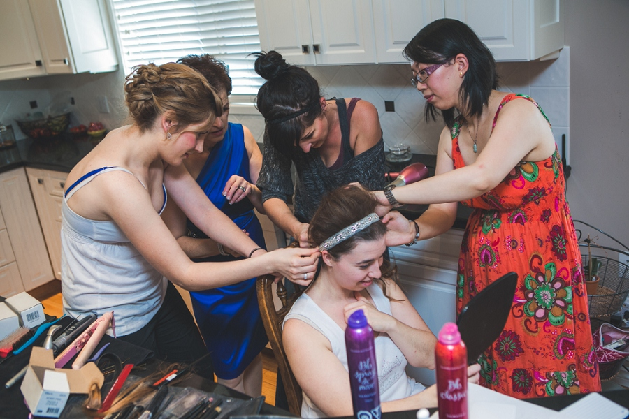 bridesmaids helping bride with hair getting ready calgary wedding photographer anna michalska peacock themed wedding