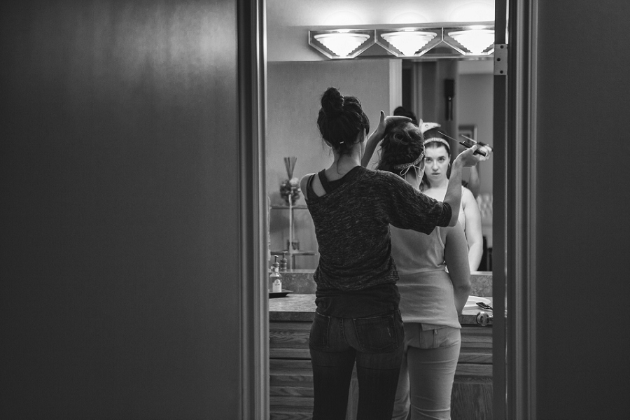 black and white of bride in mirror checking hair calgary wedding photographer anna michalska peacock themed wedding