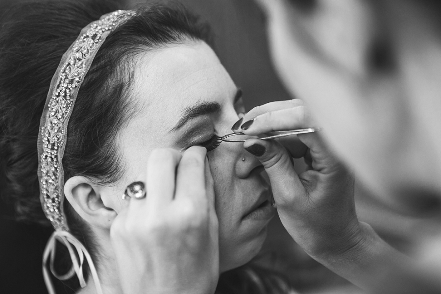 bride putting on eyelash extensions calgary wedding photographer anna michalska peacock themed wedding