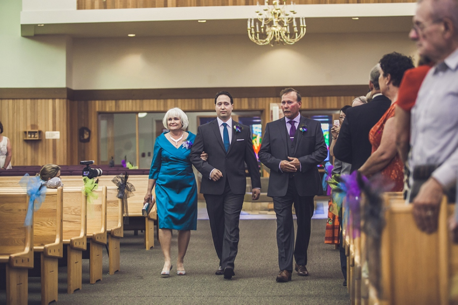 groom walking down the aisle calgary wedding photographer anna michalska peacock themed wedding
