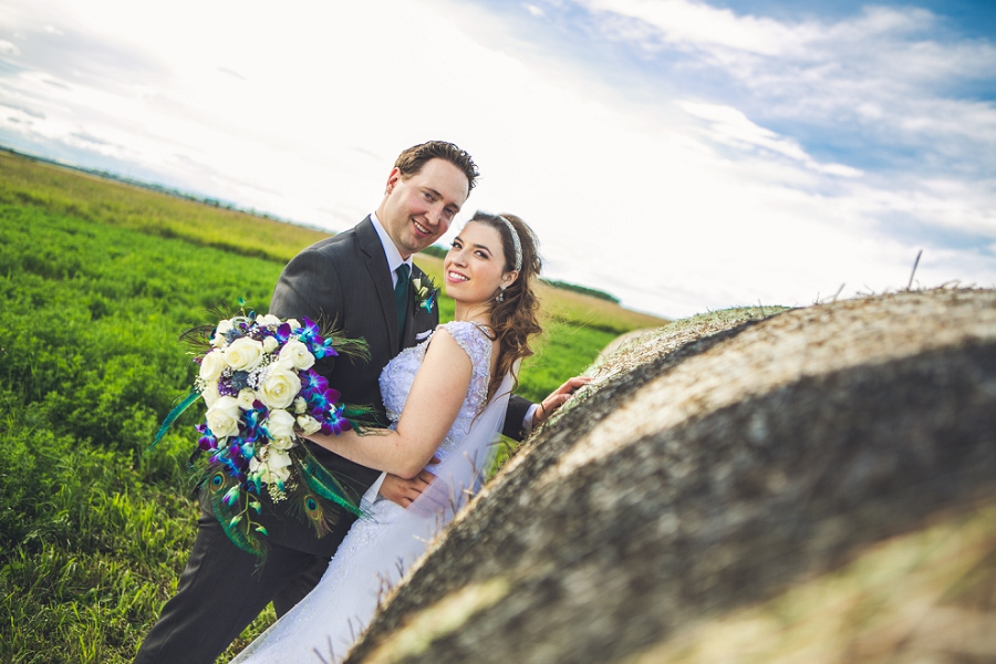 bride and groom hay barrels smiling calgary wedding photographer anna peacock themed wedding