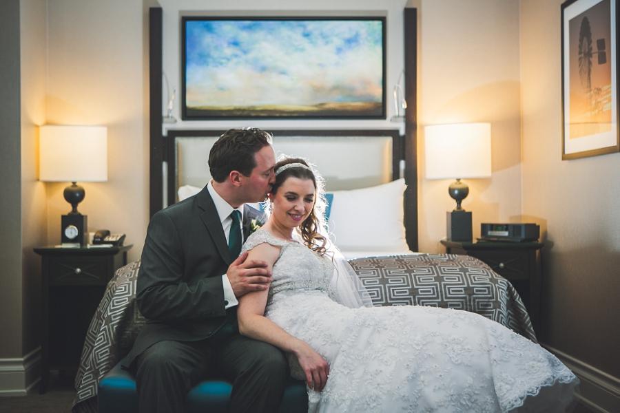 bride and groom in hotel room calgary wedding photography anna michalska peacock themed wedding