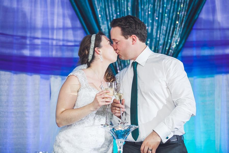 bride and groom kissing peacock themed wedding calgary anna michalska photography