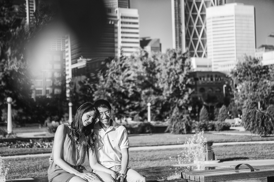 couple sitting on bench calgary engagement session central memorial park
