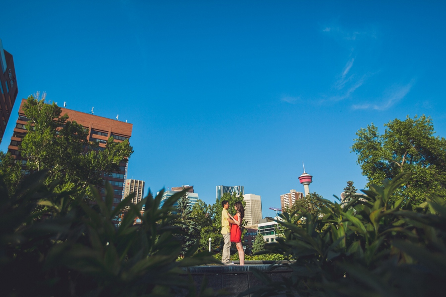 couple standing with downtown view calgary engagement session
