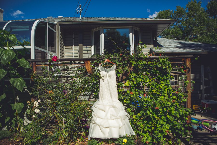 bride dress hanging in foliage calgary wedding photographers anna michalska
