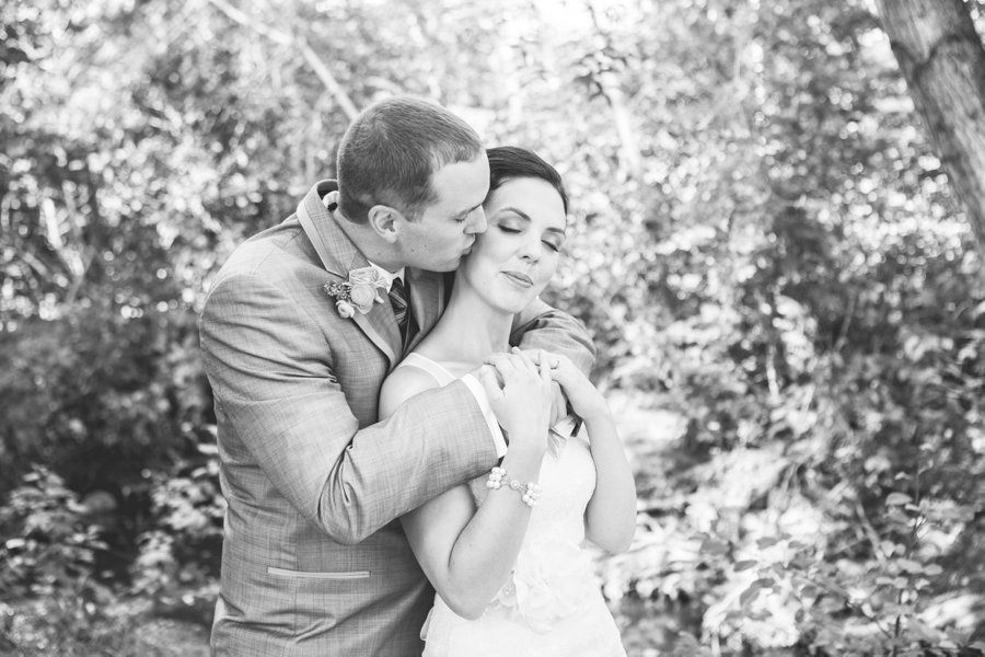 groom kissing bride confederation park calgary wedding photographers anna michalska