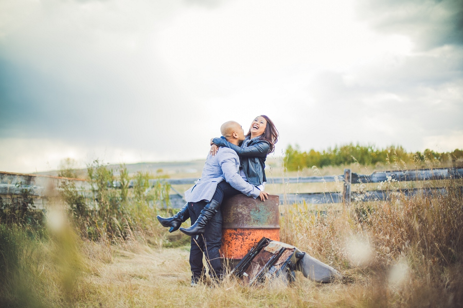 calgary cambodian engagement session couple laughing sitting on barrel