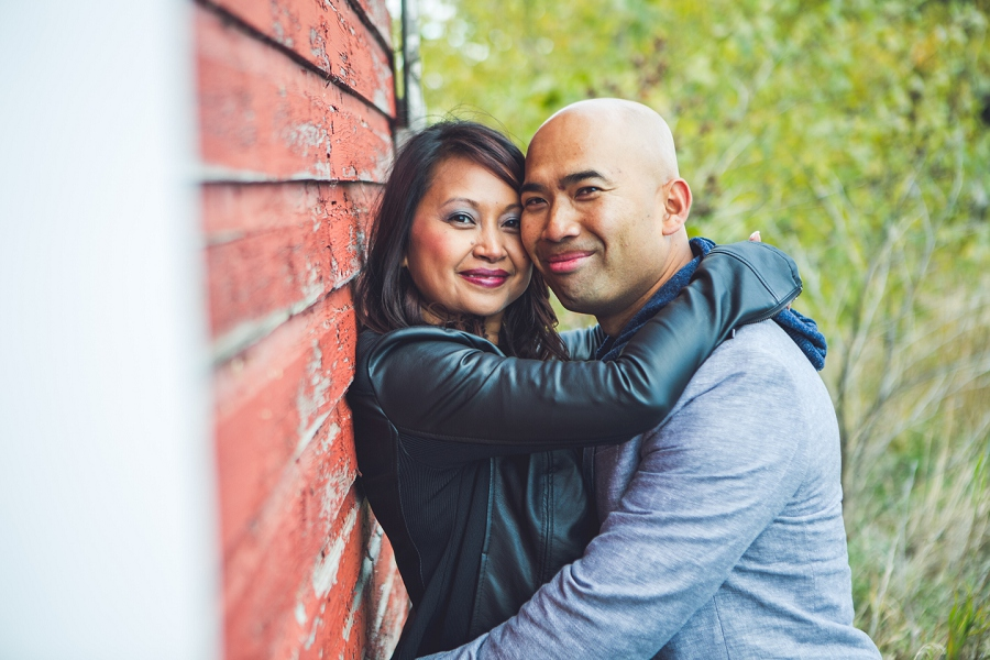 calgary cambodian engagement session rustic red barn hugging couple