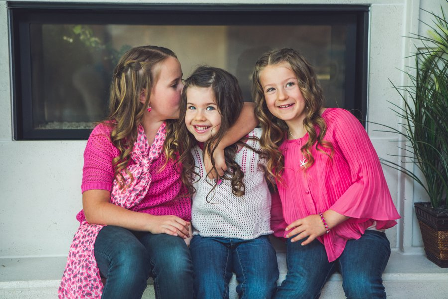 calgary family photographer girls daughters sisters by fireplace portrait