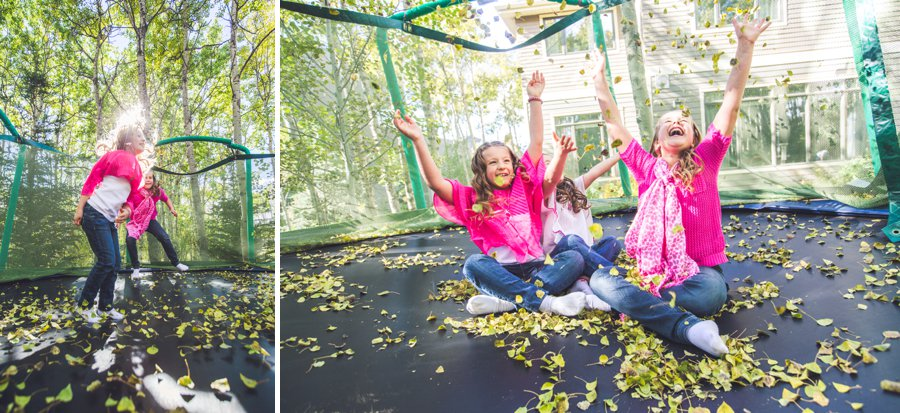 calgary family photographer trampoline throwing leaves into the air autumn fall