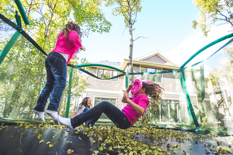 calgary family photographer three sisters on a trampoline