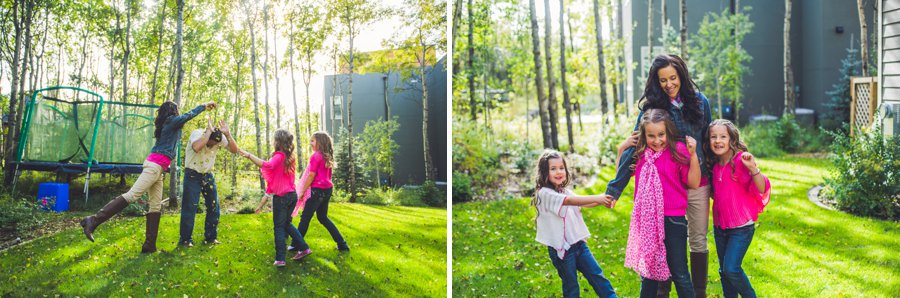 calgary family photographer mother with daughters throwing leaves on father