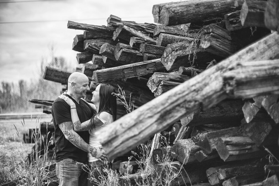 calgary biker couple engagement session photographer wood pile smiling