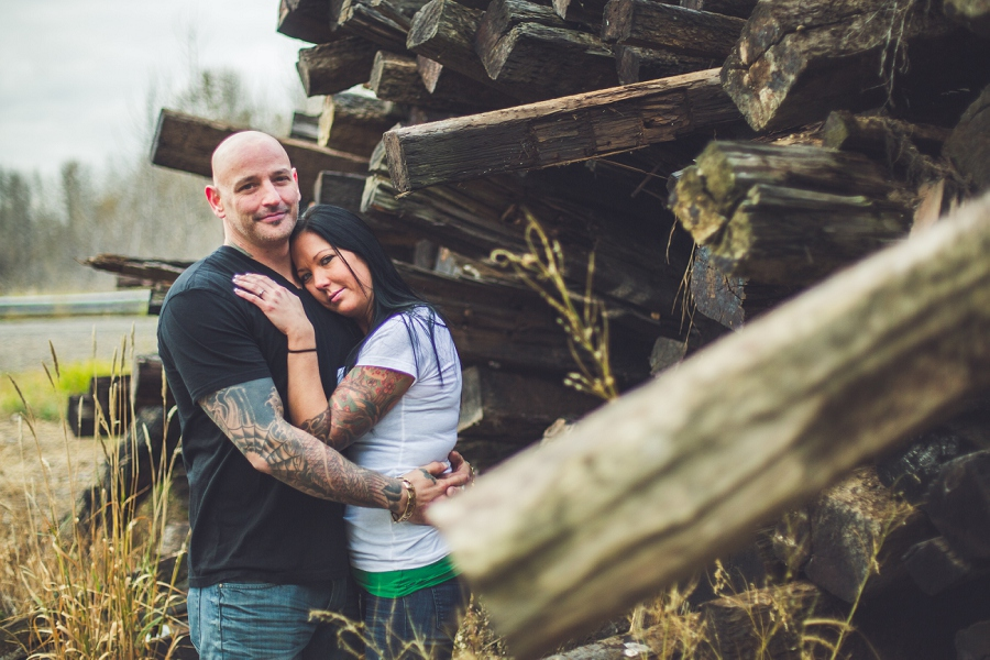 embracing by wood pile calgary biker couple engagement session photographer