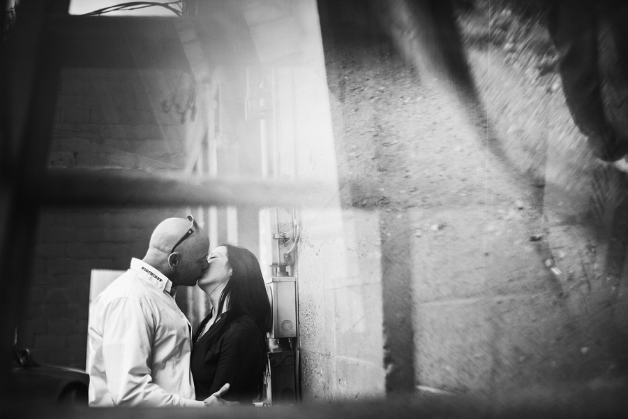 kissing through stairway back alley inglewood calgary biker couple engagement session photographer