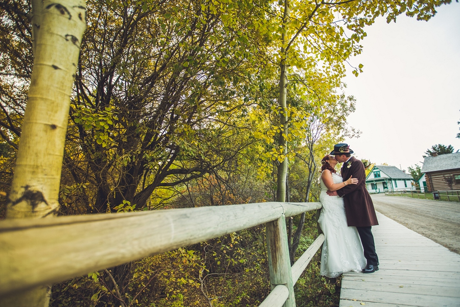 bride groom kissing under tree calgary steampunk wedding photographer anna michalska heritage park
