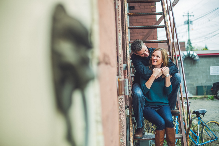 couple cuddling on stairs laughing red brick inglewood wedding anniversary photography session calgary