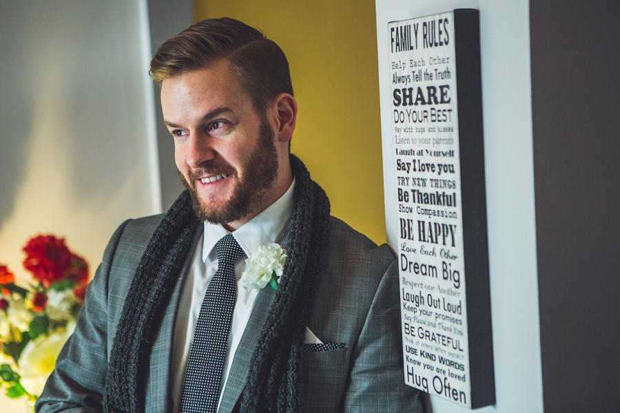 groom smiling wearing scarf calgary wedding photographer anna michalska