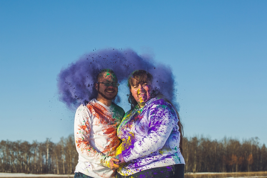 holi powder burst behind couple engagement session calgary anna michalska