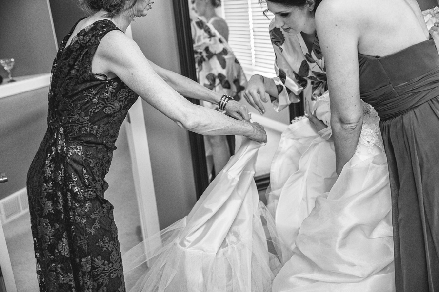 bride stepping into wedding gown calgary wedding photographer anna michalska