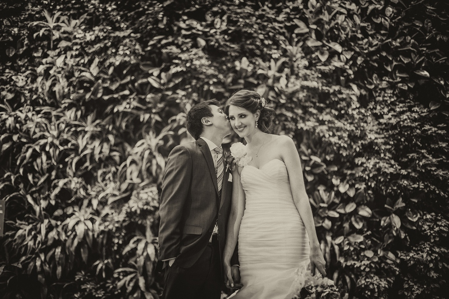 groom kissing bride living wall devonian gardens wedding