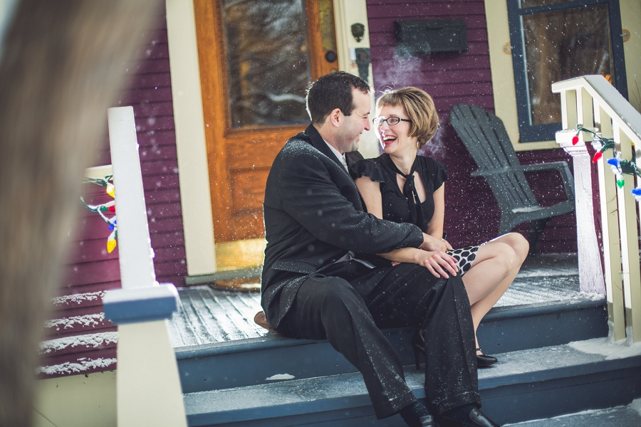 couple laughing on front steps of home winter engagement photos calgary anna michalska