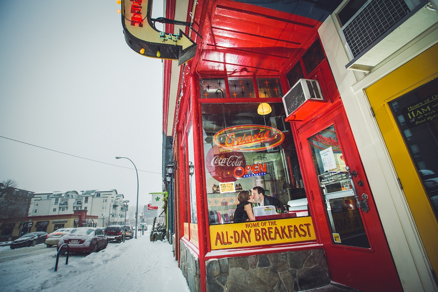 winter engagement photos couple kissing in window galaxie diner calgary anna michalska