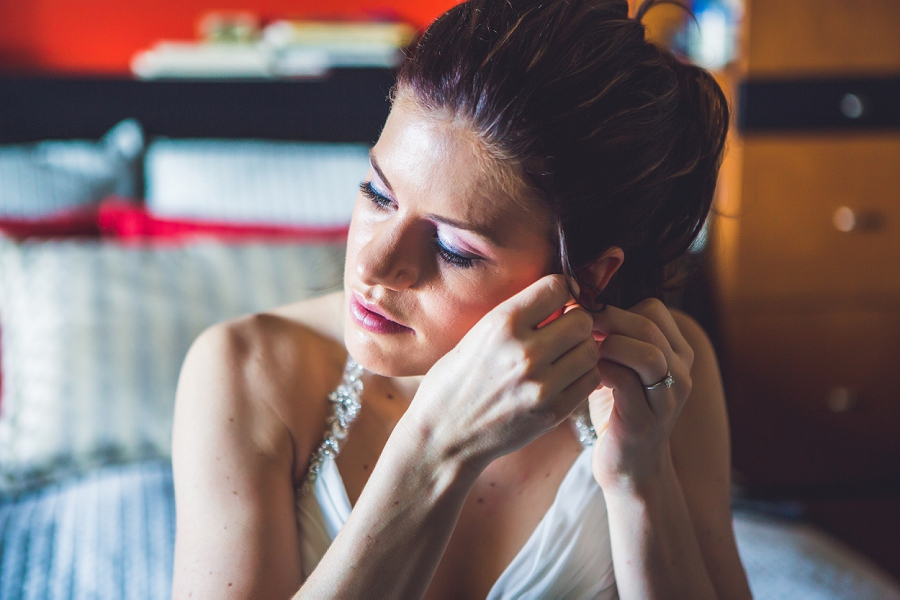bride putting on earrings calgary wedding photographer anna michalska