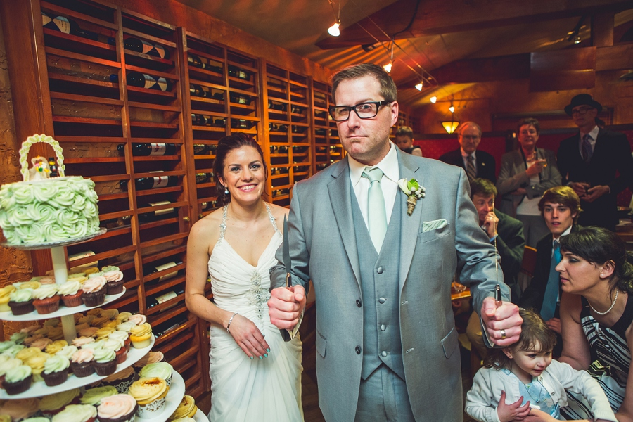 groom with cake cutting knives bonterra trattoria calgary wedding photographer anna michalska