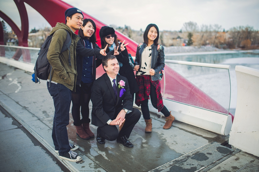 calgary wedding photographer anna michalska winter wonderland peace bridge groomsman with tourists