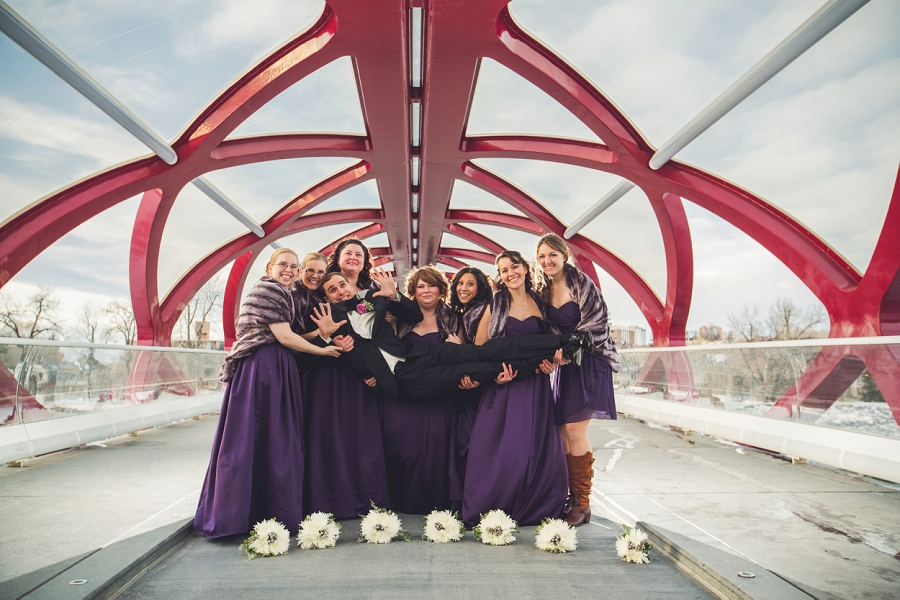 calgary wedding photographer anna michalska winter wonderland peace bridge bridal party holding groom
