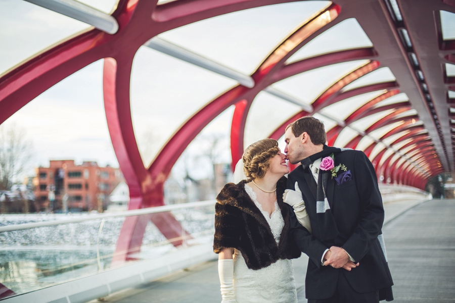 calgary wedding photographer anna michalska winter wonderland peace bridge groom kisses bride