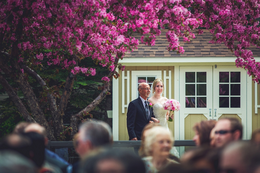 valley ridge golf calgary wedding photographer anna michalska bride sees groom for the first time down the aisle pink blossoms