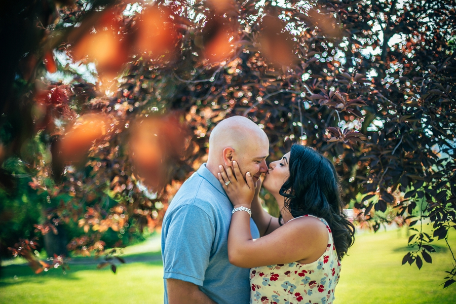 calgary rooftop engagement pictures kiss red leaves tree engagement