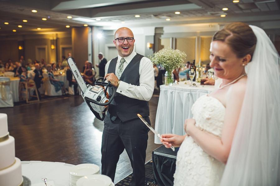 groom with chainsaw wedding cake executive royal inn calgary wedding photographers anna michalska