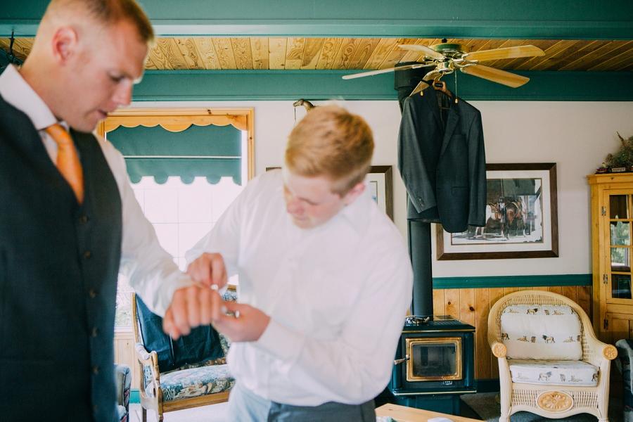 putting on cufflinks groom spring valley chapel rustic wedding alberta calgary photographer anna michalska