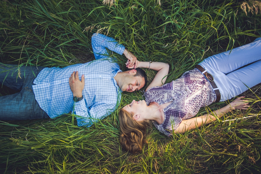 laying in grass couple sunset north glenmore park calgary engagement photos anna michalska wedding summer