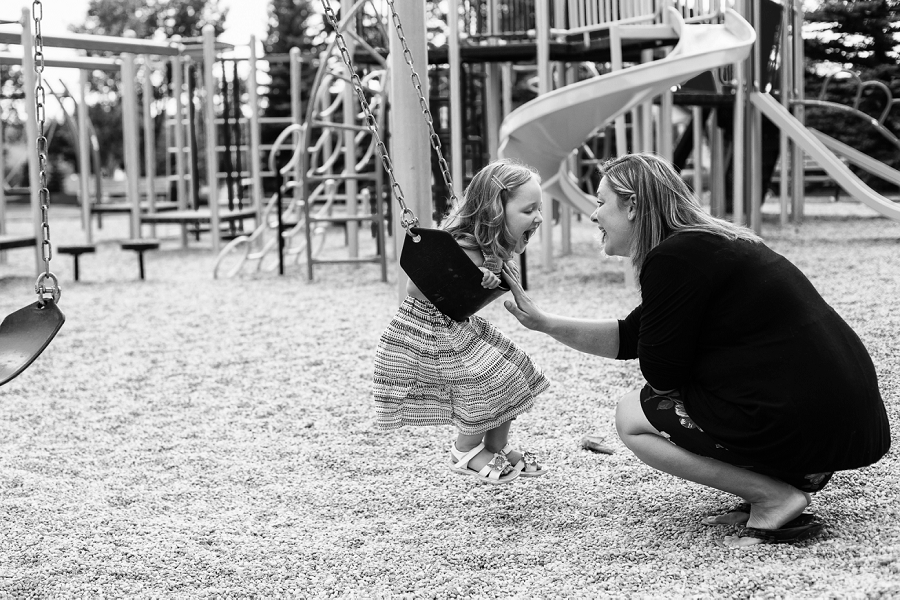calgary family photographer candid family photos girl on swing with mother