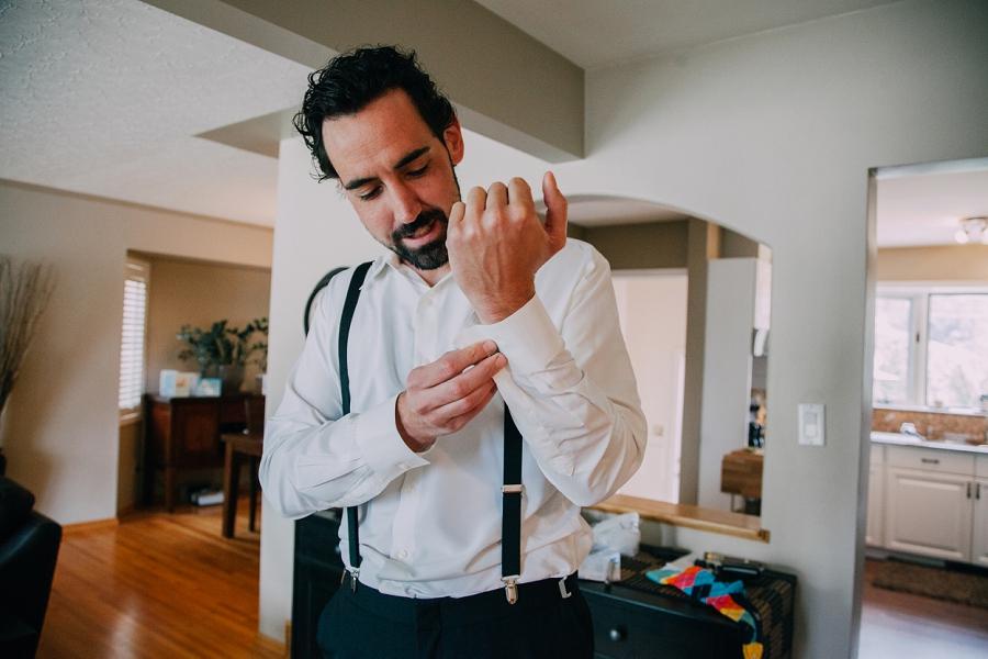 groom doing up cufflinks calgary wedding photographers anna michalska